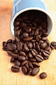 Roasted coffee beans falling out of a beaker