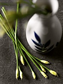 Chinese chives beside a vase