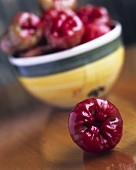 Rose apple in front of a bowl of rose apples