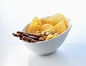 Nibbles in a bowl (salted sticks, peanuts, crisps)