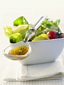 Spoonful of dressing lying on bowl of salad