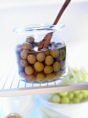Green olives in a storage jar in the fridge