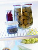 Plastic containers and preserving jar in fridge