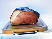 Smoked ham on chopping board in fridge