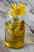 Arnica essence and Arnica flowers in a glass bottle