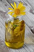 Arnikaessenz und Arnikablüten in einer Glasflasche