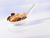 Quail appetiser with lentils and fig on a porcelain spoon