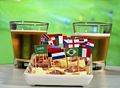 Ham and cheese on sticks with flags and beer in front of TV