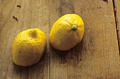 Two lemon halves on a wooden background