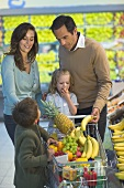 Family at the fruit counter in a supermarket