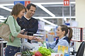 Young couple paying at supermarket check-out
