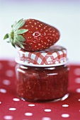 A strawberry on a full jam jar