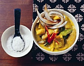 Mango curry with banana, peppers and coconut flakes