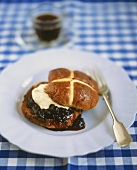 Hot cross bun with blueberries and cream