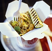 Pork with noodles and cashew nuts in take-away box