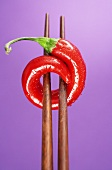 A chilli on chopsticks, purple background
