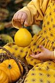 Girl holding a baby pumpkin (detail)