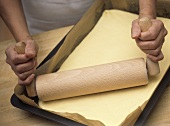 Rolling pin with folding handles on yeast dough in baking tray