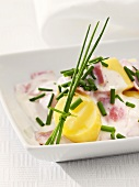Potatoes with ham and sour cream sauce and chives