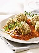 Crispy green spelt and sesame balls on tomato sauce