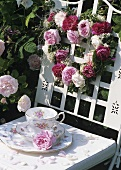 Rose-patterned coffee things and heart of roses in garden
