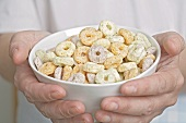 Hands holding a bowl of cereal rings
