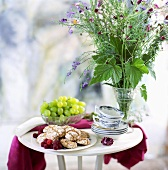 Almond biscuits, raspberries, grapes, cups & saucers on a table