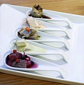 Assorted herring appetisers on china spoons