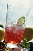 Pomegranate juice with ice cubes & slice of lime in glass
