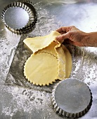Using a baking tin to cut out pastry for tarts