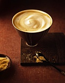 Milky coffee in a bowl, brown sugar in front
