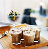 Milky coffee in glasses on tray