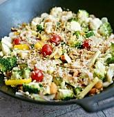 Vegetables, shrimps, grated coconut, sunflower seeds in wok