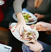 Woman reaching for appetiser (herring terrine on flatbread triangle)