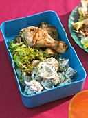 Grilled chicken leg with potato salad in picnic box