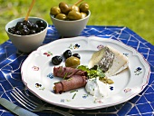 Appetiser plate with roast beef, cheese and olives