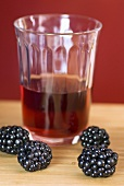 Glass of blackberry juice and fresh blackberries