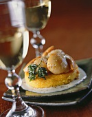 Polenta cake topped with scallops, two glasses of white wine