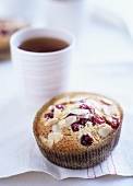 Cranberry and almond bun and a beaker of tea