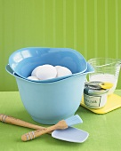 Fresh eggs in mixing bowl surrounded by baking utensils