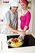 Mann hält Frau davon ab vom Obstkuchen zu naschen