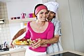 Mann greift nach Obstkuchen in den Händen einer Frau