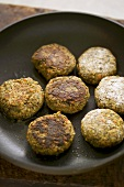 Lentil burgers being fried in a frying pan