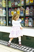 Little girl outside a sweetshop in Rye, Sussex, England