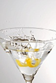 Piece of lemon peel falling into a glass of Martini