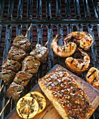 Salmon, beef kebabs and prawns on barbecue