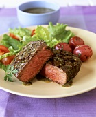 Beef fillet steak with herb sauce and salad
