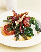 Green asparagus, spinach and tomato salad with fried bacon