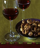 A small dish of roasted nuts and two glasses of red wine