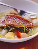 Fried red mullet on a bed of vegetables